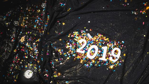 2019 яркие цифры между конфетти на темной ткани