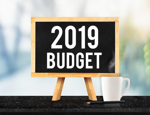 2019 budget on blackboard with easel on black marble table with coffee cup on blur office