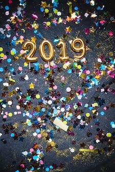 2019 свечей между разноцветными конфетти