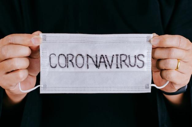 Закройте вверх по рукам держа хирургическую маску с текстом коронавируса написанным на ем. вирусная инфекция 2019-нков в городе ухань. covid-19 (sars-cov-2) распространился по всему миру. воздействие пандемического вируса.