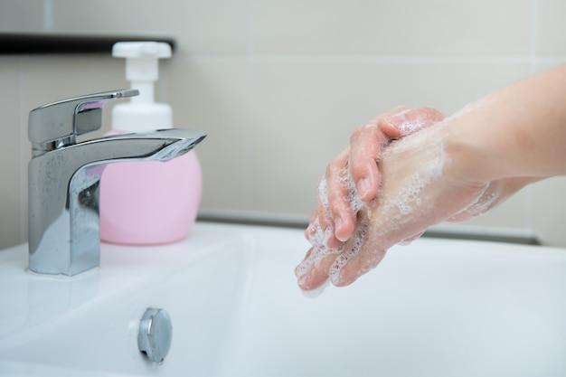 液体ハンドウォッシャー石鹸を使用して手を洗う女性、コロナウイルス2019、covid-19ウイルスの感染リスクから保護します。