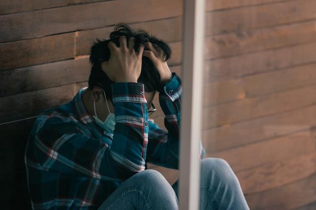 アジアの男性の仕事は、自宅での失業からストレスを受けて座っている保護マスクを着用します経済危機の概念、人々の失業およびコロナウイルス病2019またはcovid-19の生産。