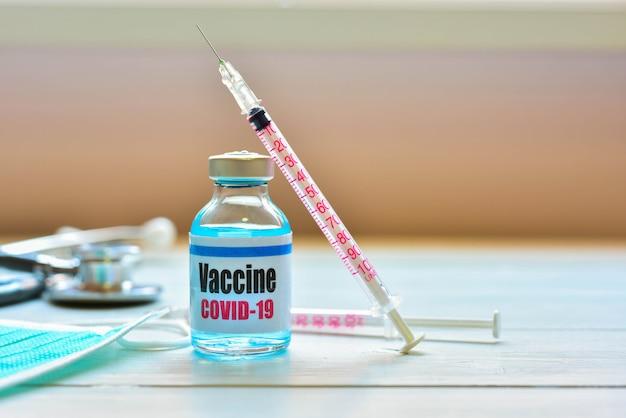 コロナウイルス感染からの予防と治療のためのワクチンバイアルとシリンジ注射-コロナウイルス病2019、covid-19ワクチンのコンセプト。