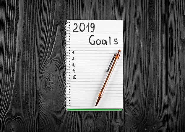2019 goals on his notebook. new year resolutions concept. top view.