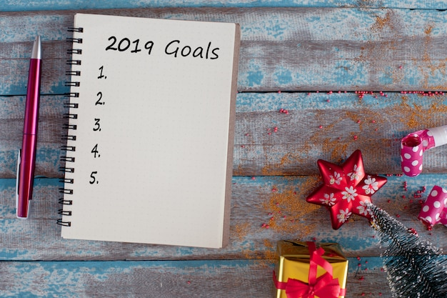 2019 goals list with notebook and pen on rustic blue wooden table