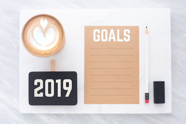 2019 goals on recycle paper with pencil ,clip blackboard, pencil, eraser and coffee cup