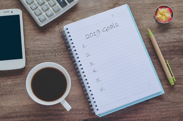 2019 goals text on book note with cup of coffee, pen and smartphone.