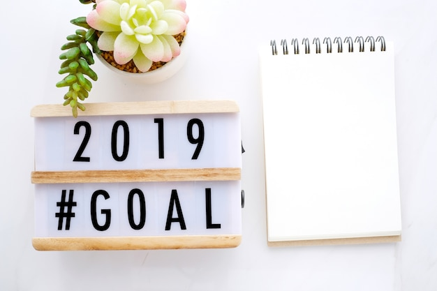 2019 goals on wood box and blank notebook paper on white marble background