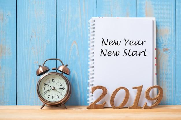 2019 happy new year new start text on notebook, retro alarm clock