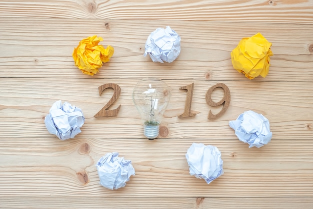2019 happy new years with lightbulb with crumbled paper