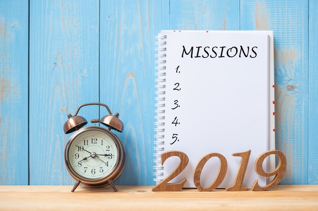 2019 happy new years with mission text on notebook, retro alarm clock