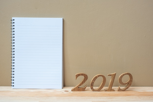 2019 happy new years with notebook and wooden number on table