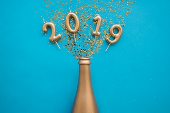 2019 inscription from candles with bottle on table