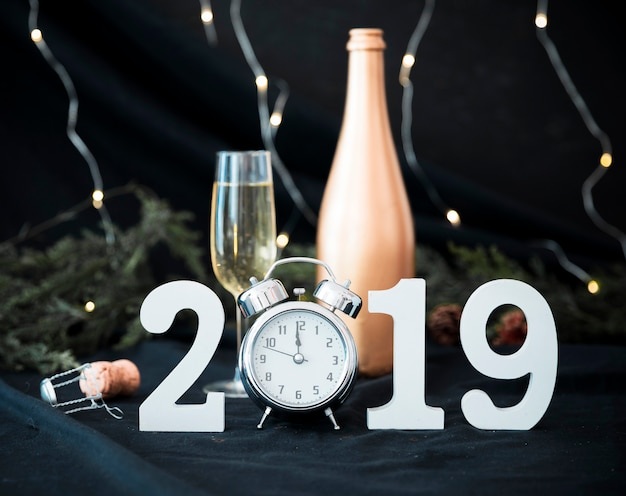 2019 inscription with clock and glass on table