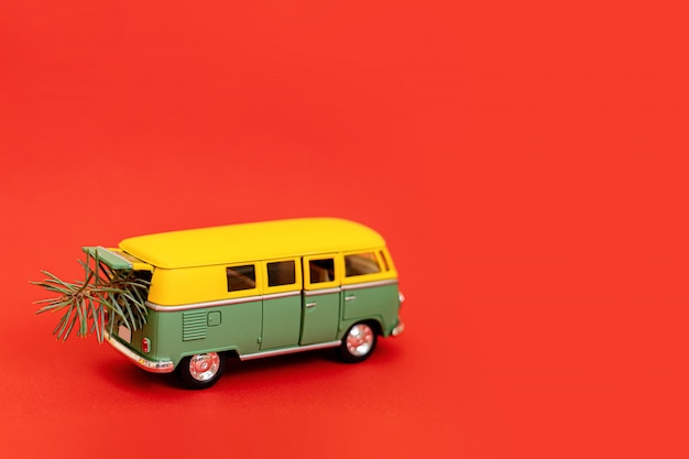 2019 miniature hippy car with fir tree on red background