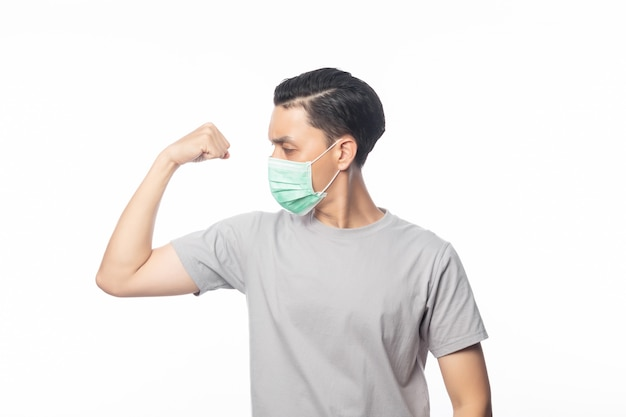 感染を防ぐ強さを示す衛生マスクの若いアジア人男性、2019-ncovまたはコロナウイルス。午後2.5の戦闘や白い背景のflu.onなどの空中呼吸器疾患