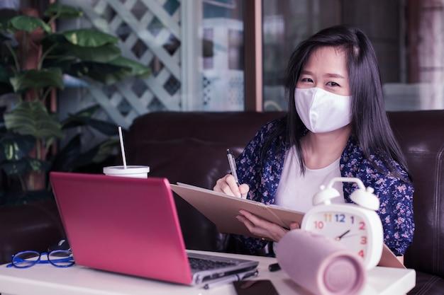 Женщина работая на компьтер-книжке дома с защитной маской износа медицинской для защищает для защищает 2019 - ncov, covid 19 или вирус короны. wfh или работа от домашней концепции.