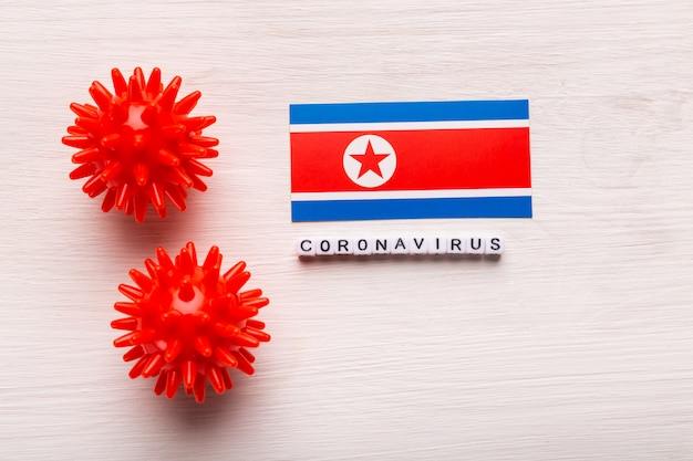 テキストと2019-ncov中東呼吸器症候群コロナウイルスまたはコロナウイルスcovid-19のウイルス株モデルを抽象化し、白い背景の上の北朝鮮にフラグを立てます。ウイルスのパンデミック保護の概念。
