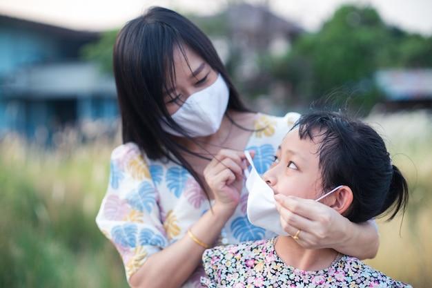 母は保護のために医療用マスクを着ている娘を助けます2019-ncov、covid 19またはコロナウイルス