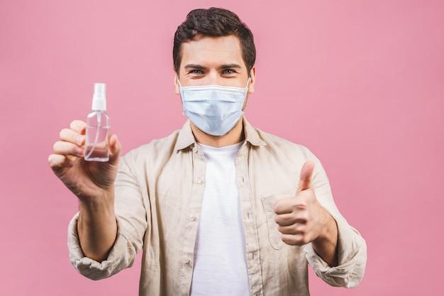 ピンクの壁に分離された滅菌フェイスマスクの若い男。流行性パンデミックコロナウイルス2019-ncov sars covid-19インフルエンザウイルスのコンセプト。アルコール液体抗菌消毒剤が入ったボトル。