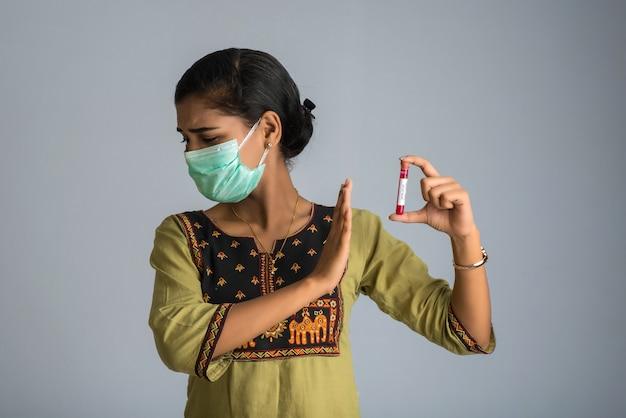 コロナウイルスまたは2019-ncov分析用の血液サンプルのテストチューブを保持している女性。