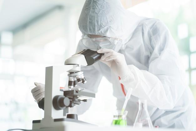 2019-ncovワクチンまたは血清の研究室で顕微鏡スライドを分析する医学者