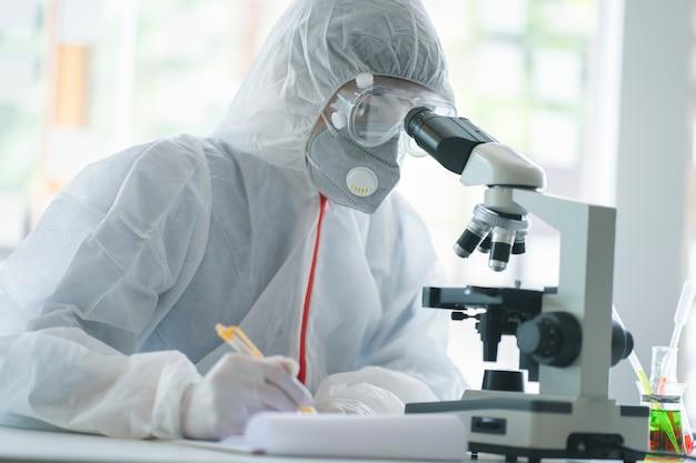 2019-ncovワクチンの研究室で顕微鏡スライドを分析する医学者