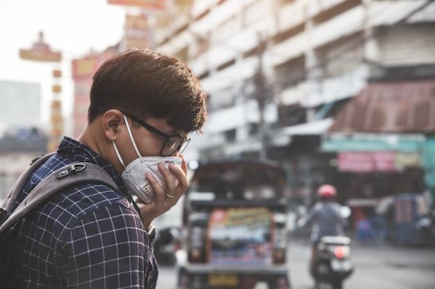 コロナウイルス検疫の概念。新規コロナウイルス2019-ncov。都市の医療フェイスマスクを持つ男。