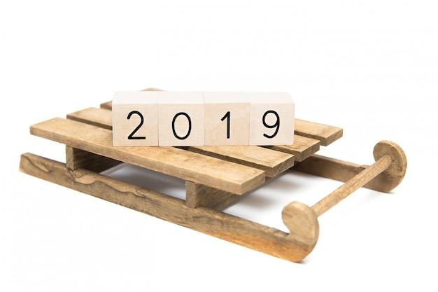 Новогодняя открытка на 2019 год. деревянные кубики 2019 на санях на белой предпосылке. изолированные o