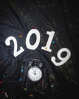 2019 new year figures above alarm clock
