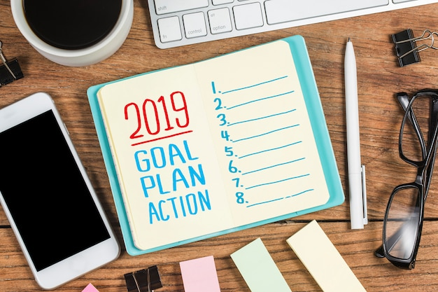 2019 new year goal,plan,action text on notepad with office accessories.