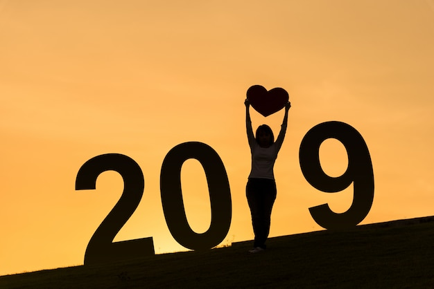 2019 new year silhouette of asian lady standing on hill and holding heart