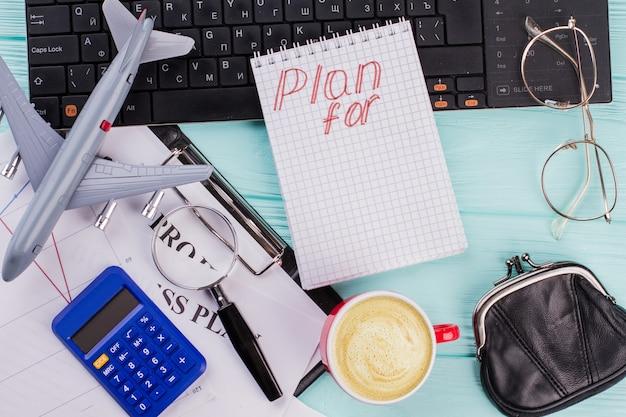 2019年は、木製のテーブルトップの背景に旅行者用アクセサリーのメガネ財布と飛行機を備えたノートブックを計画しています。フラットレイ旅行のコンセプト。