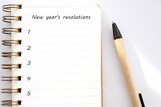 2019 resolutions on blank notebook paper on white marble background