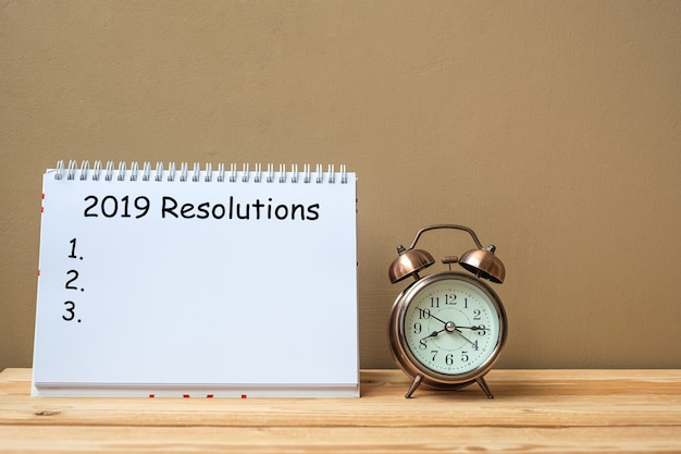 2019 resolutions text on notebook and retro alarm clock on table