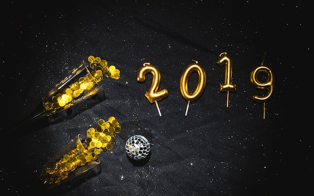 2019 shaped candles with glasses of confetti