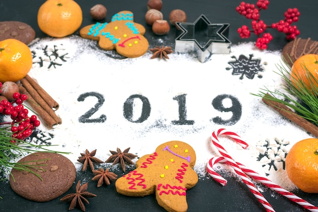 2019 text made with flour with decorations on black background.