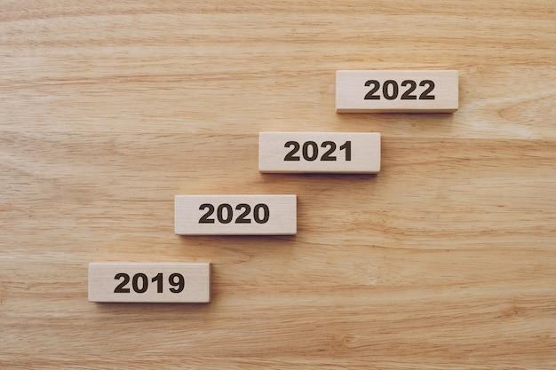 2019年から2022年までの木製テーブルの背景にウッドブロックで新年あけましておめでとうございます。新年のコンセプト