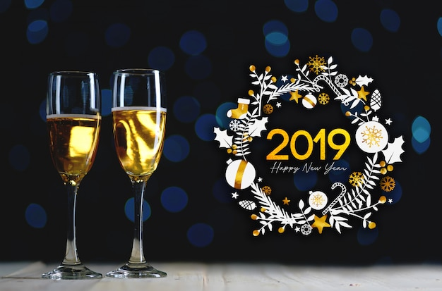 2019 typography art. two glasses of champagne dark glow lights background