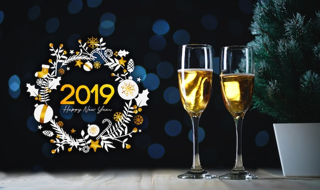 2019 typography art. two glasses of champagne and small christmas tree dark glow lights background