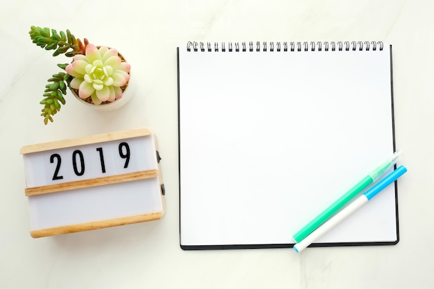 2019 on wood box, blank notebook paper on white marble table background