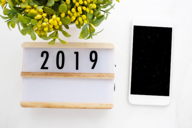 2019 wood box and smart phone with blank screen on white marble background