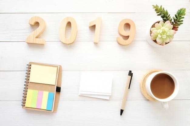 2019 나무 편지, 빈 노트북 종이, 명함 및 흰색 테이블 backgroun에 커피