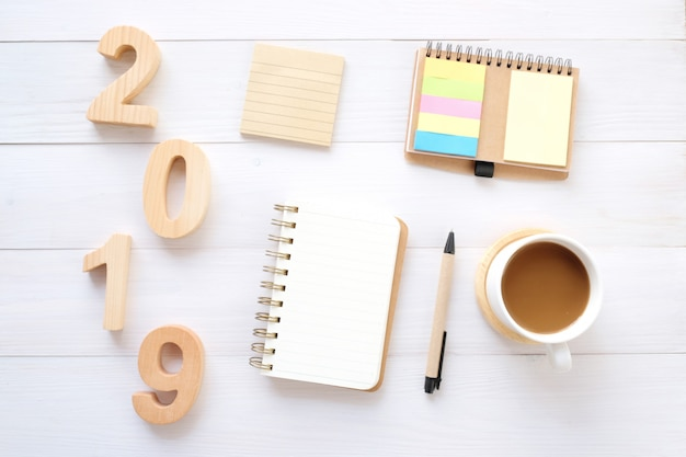 2019 wood letters, blank notebook paper and coffee on white table background