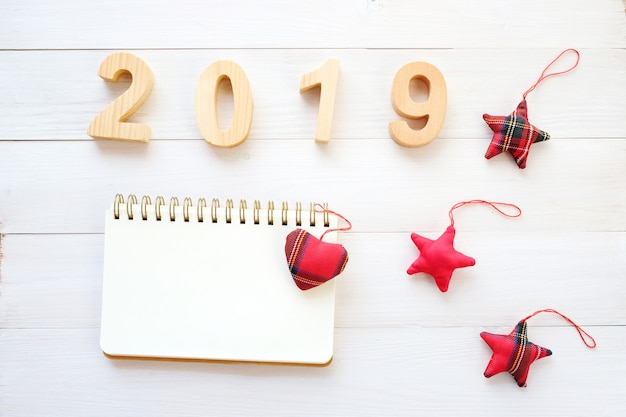 2019 wood letters, blank notebook paper and ornament on white wood background