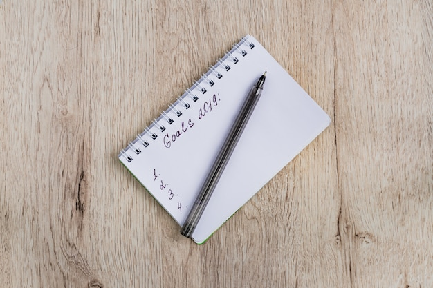 ビジネスおよびオフィスコンセプト-空白のノートブックと木製のテーブルに黒のペン。目標2019。最小限の平干し、上面図。