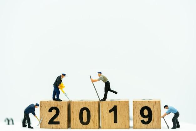 Миниатюрные люди: работник копать деревянный ящик с номером 2019. сервис, ремонт и техническое обслуживание концепции.
