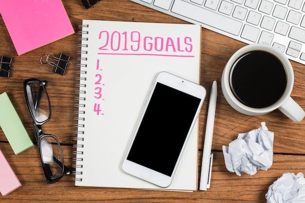 2019年の新年の目標、計画、オフィスの付属品を備えたメモ帳のアクションテキスト