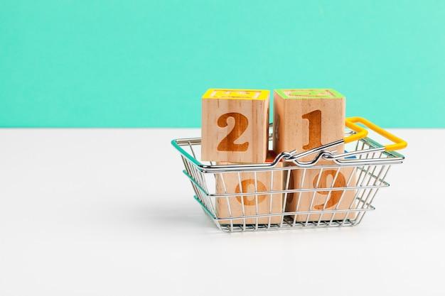 白いテーブルの上のショッピングカートトロリーと2019年