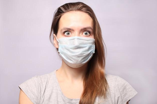 Молодая женщина носит респираторную защитную маску. жвачка поседела от страха и выглядит большими испуганными глазами. эпидемия гриппа, аллергия на пыль. коронавирус 2019 нков.